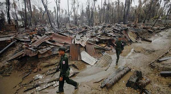 Burmese military amid burned Rohingya villag
