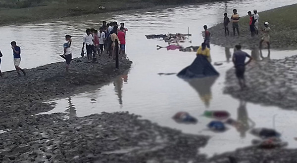 Bangladeshi onlookers stand next to the bodies of Rohingya refugees that washed up during low tide on September 1, 2017 after their boat capsized